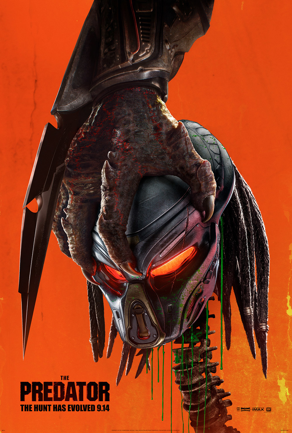 The Predator  poster, with the hand of a large predator holding the trophy head and spine of a smaller predator.