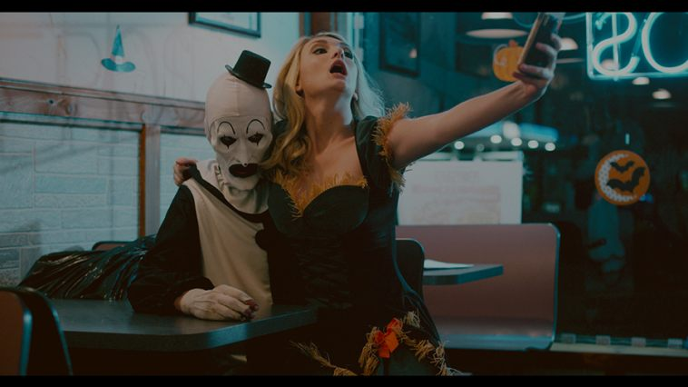 It's actually refreshing to see a horror film embrace modern technology without making it the gimmick of the entire film. A woman in a sexy scarecrow costume forces a selfie moment on Art the Clown.