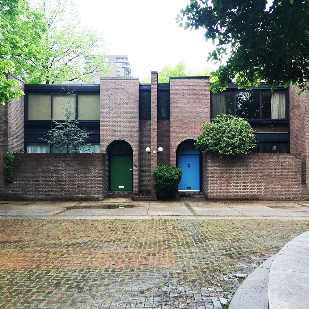 Photo of Bingham Court as it looks today. This is a view showing mirrored units with their unique colored doors and private yards.