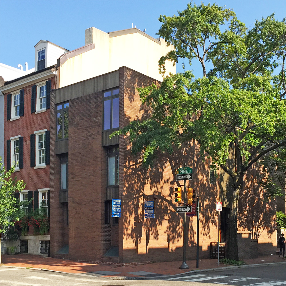 View of a Brick Modern home from the adjacent corner of 5th and Pine Streets with minimal fenestration along the street wall.