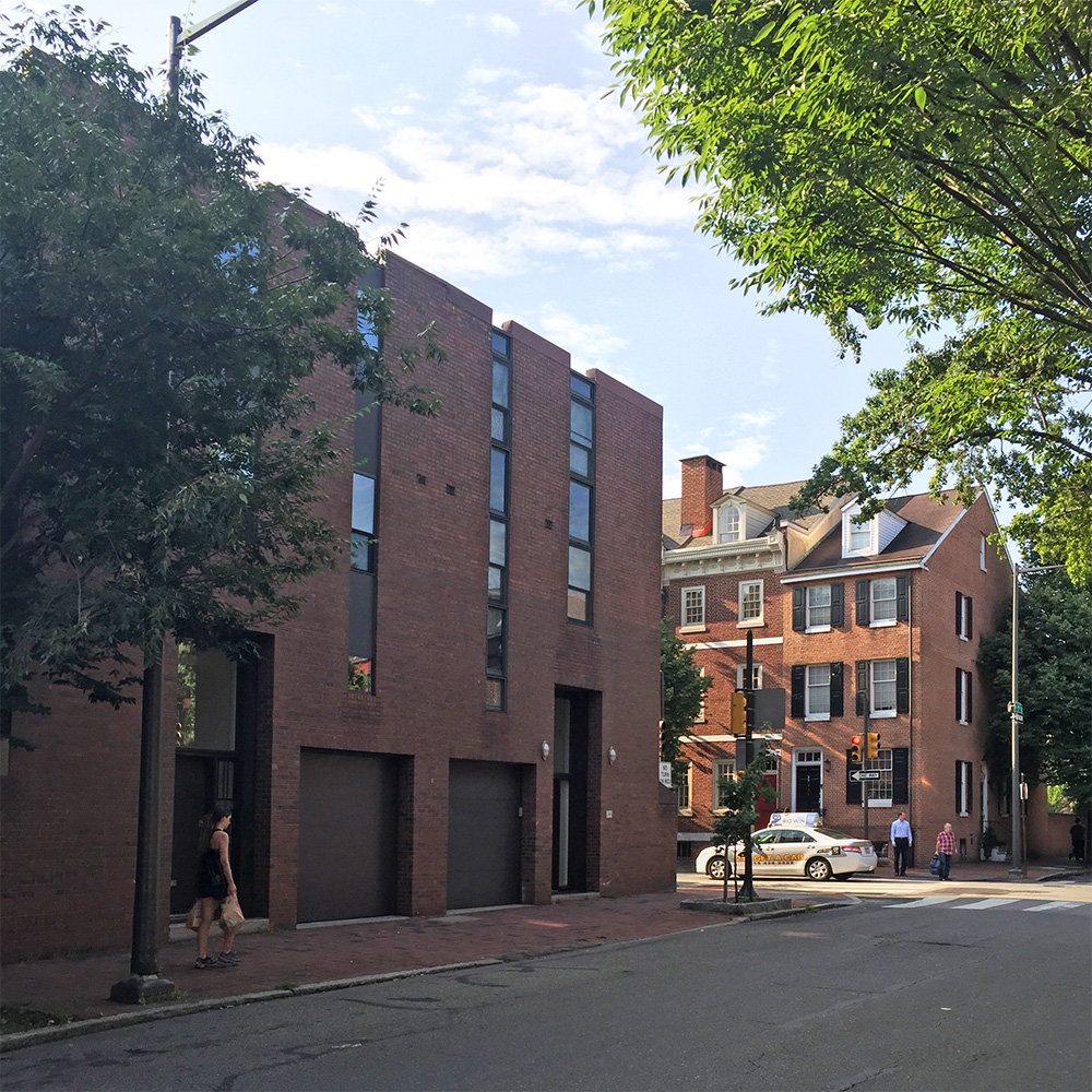 Photo of a Brick Modern building from the late sixties and adjacent colonial houses.