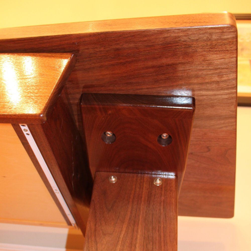 This view from below the desk top shows the bolts – not screws - that connect the legs to the upper supports and the upper supports to the top. This desk can be completely broken down into its main components for transport