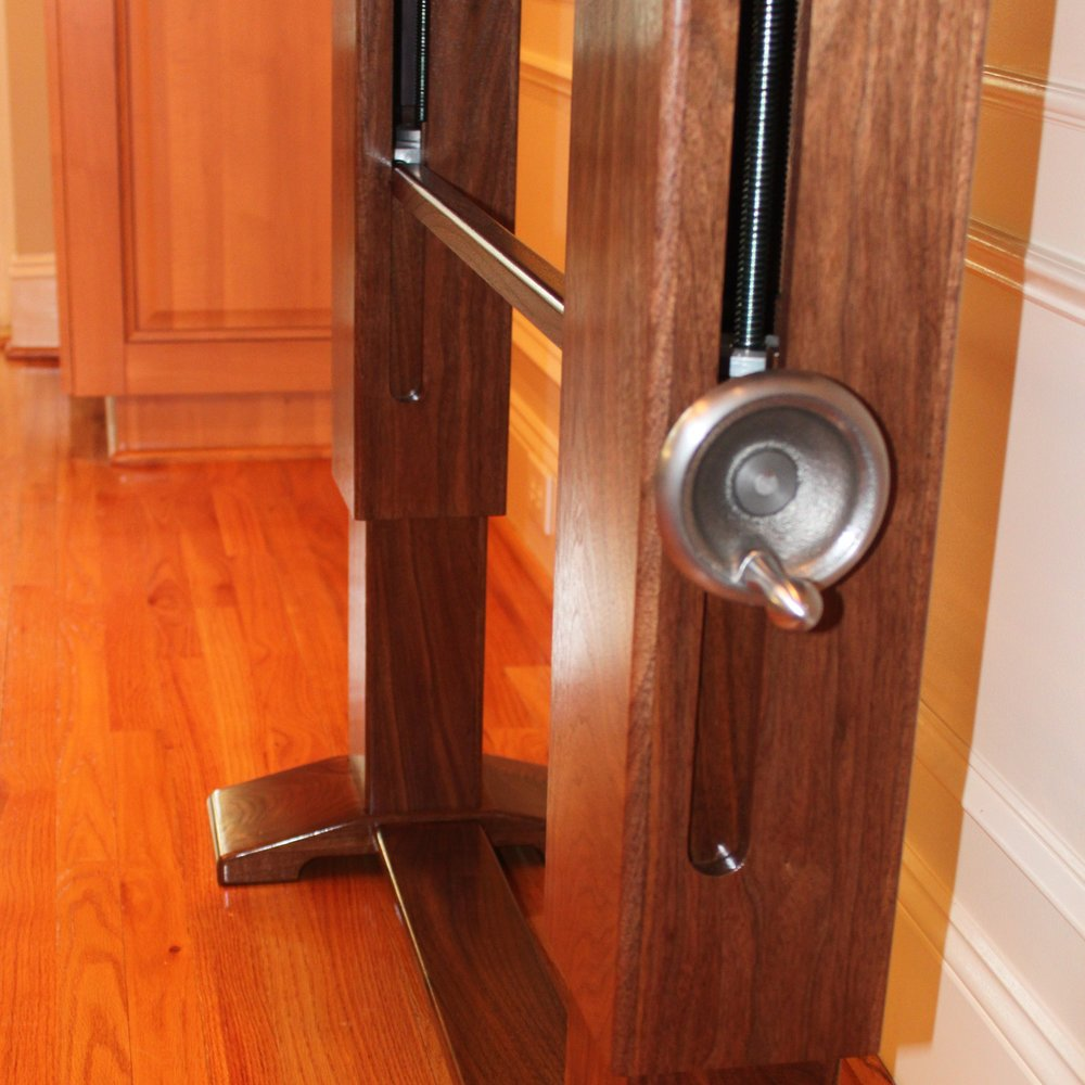 The lifting mechanism consists of a pair of custom-manufactured screw jacks embedded within each leg of the desk, connected by a steel rod. The outer leg conceals the hardware and slides along the inner leg which houses the screw jacks.