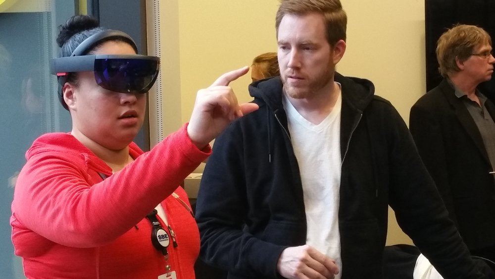 Microsoft's Ben Porter (right) shows students how to navigate the HoloLens interface.