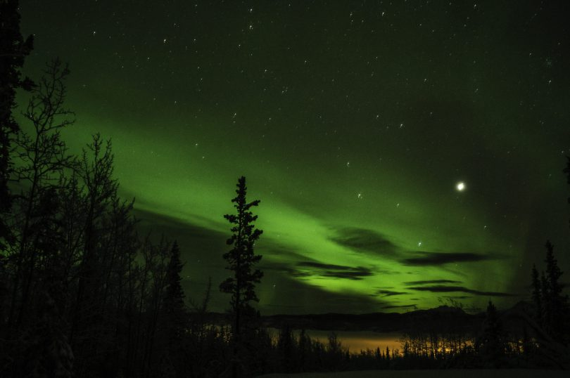 The orange glow is from the city lights below, the green is all northern lights.