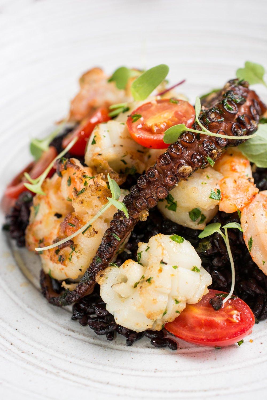 Arroz negro estilo mediterrâneo com folhas de azedinha da serra carioca e frutos do mar