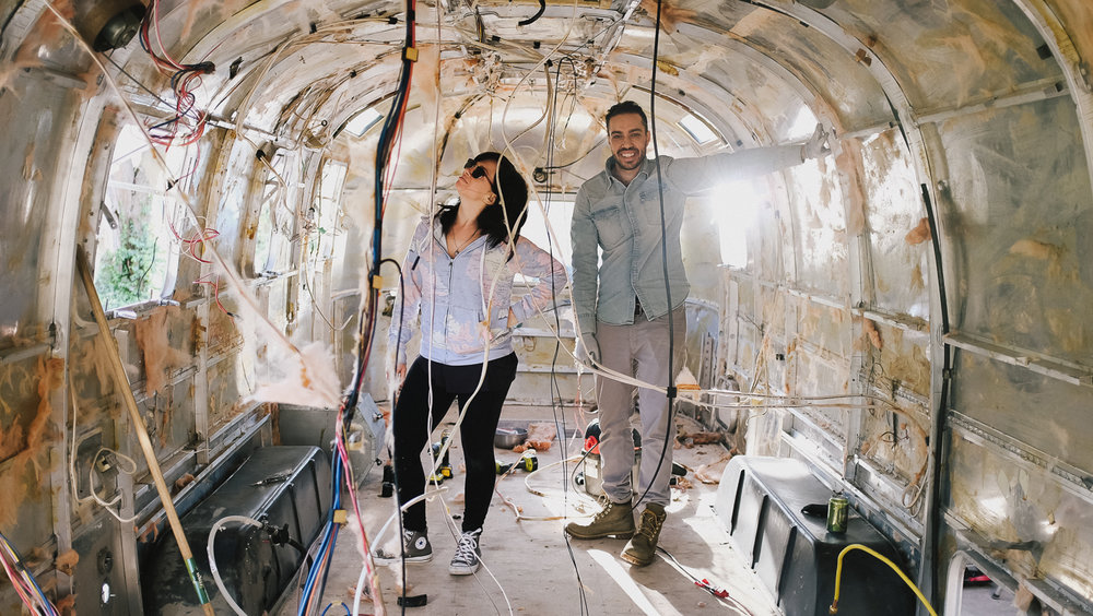Kristen and Siya, standing in their Airstream home.