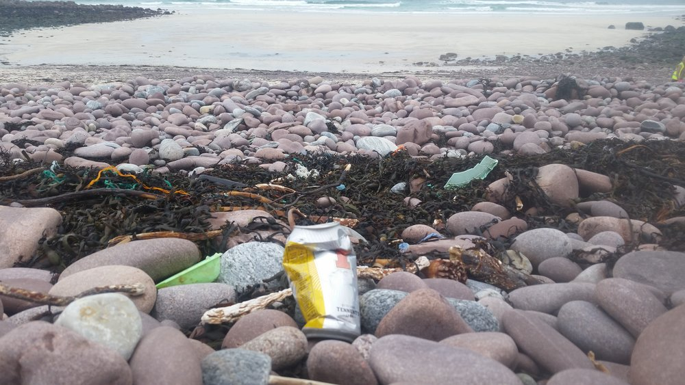 The Plastic Tide line littered with plastic and rubbish, the sandy area is visible at the top of the picture.