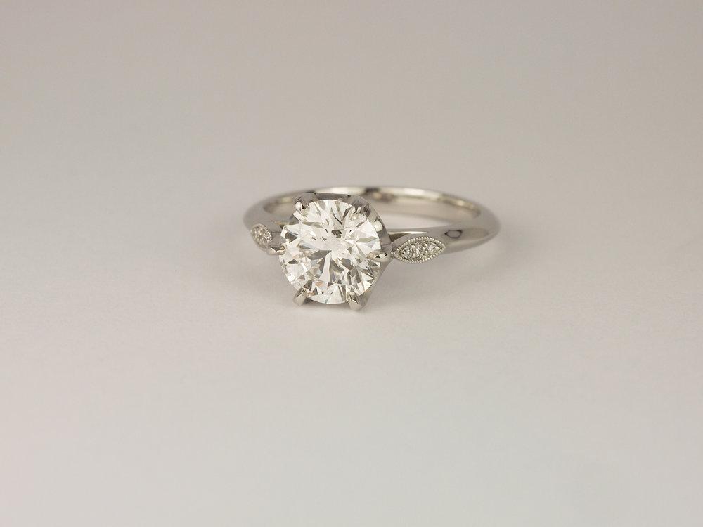 Platinum diamond engagement ring with millegrain detail