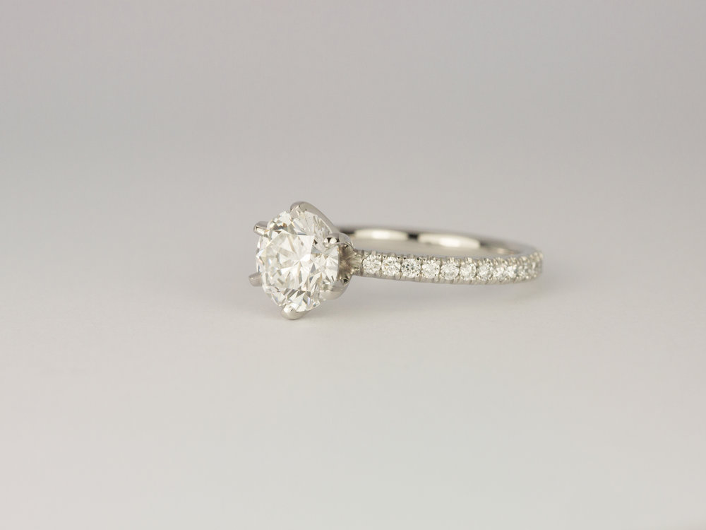 Six claw diamond and platinum engagement ring with a microset diamond band