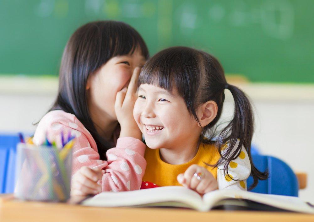 cute little girls whisper to sister
