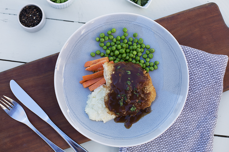 151. Classic Chicken Schnitzel served with potato mash and gravy, carrots and peas with a lemon and garlic dressing
