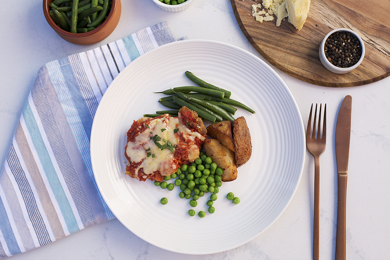 184. Classic Chicken Parmigiana served with potato, peas, green beans and topped with mozarella cheese