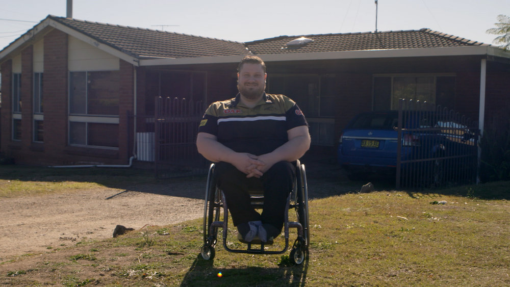 Nathan at home in Penrith (above) and with a young local fan at the 2018 State of Origin Wheelchair Rugby League game (right).
