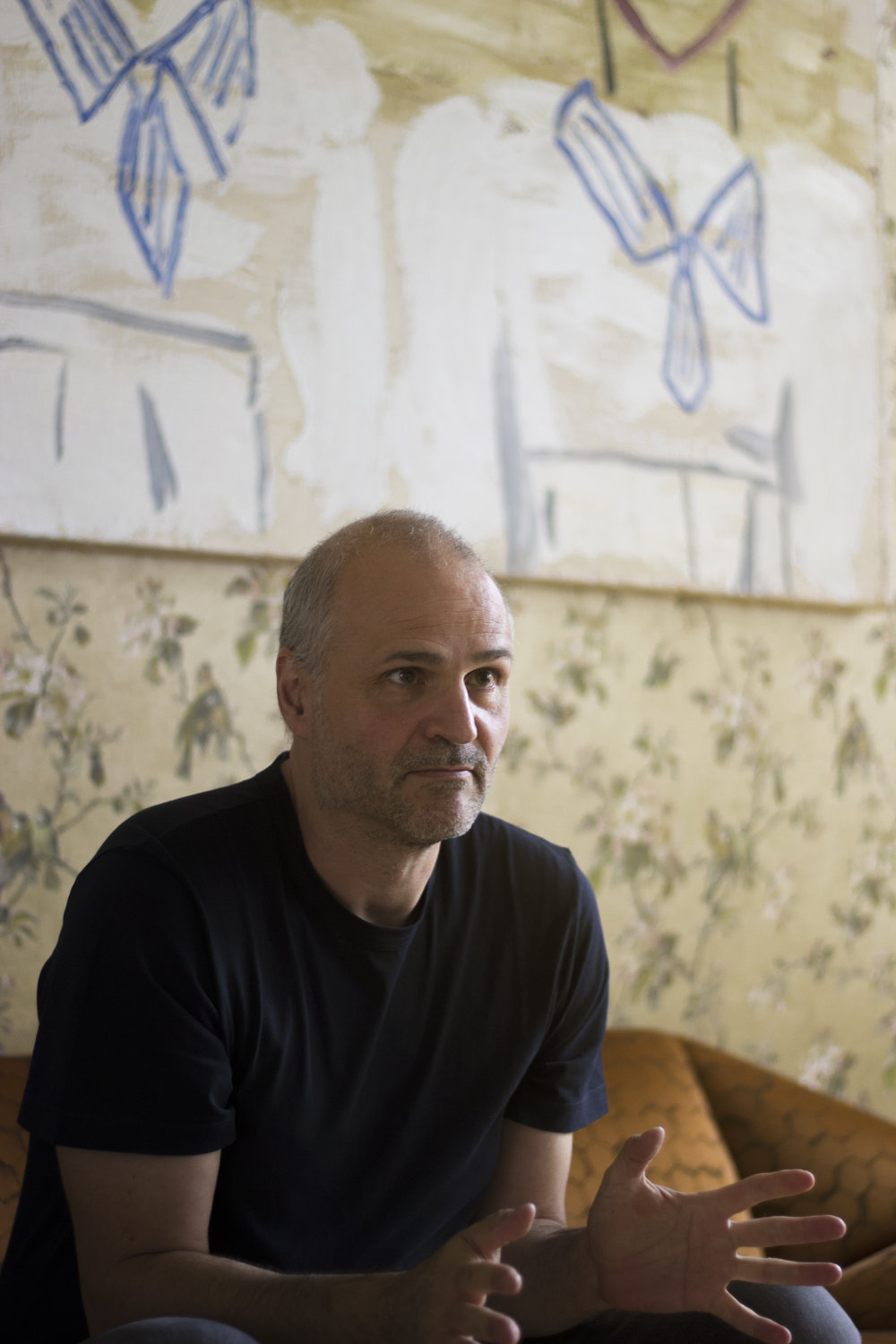 Giovanni Springmeier in his home in Berlin. Work by Rose Wylie.