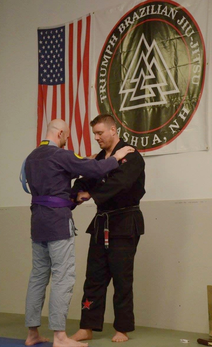 Professor Fain (pictured right) awards a purple belt to one of his students.