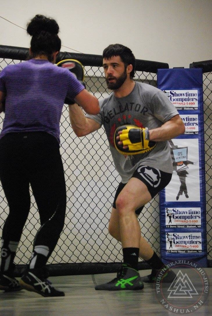 MMA coach Dennis Olson holds mitts during boxing class in our MMA cage.
