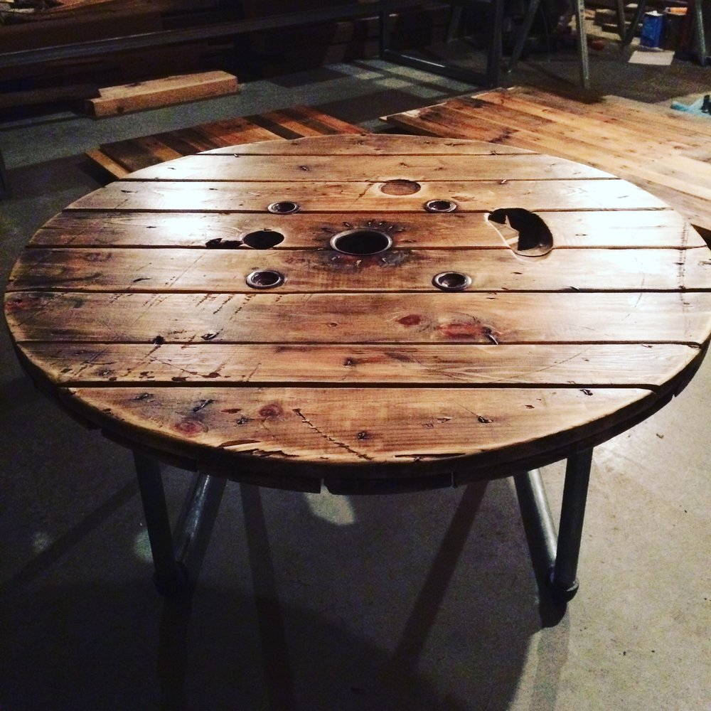 "Salvaged 48"" diameter spool coffee table on pipe legs"