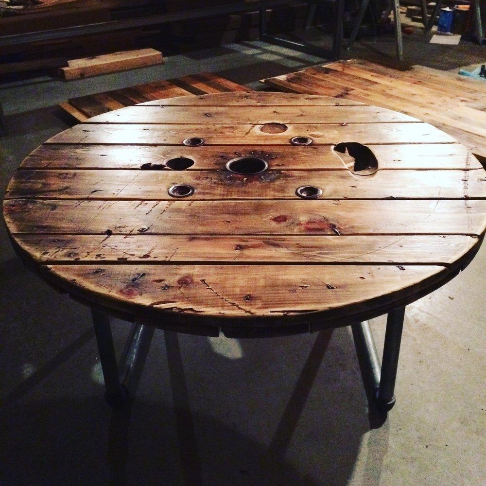 "Salvaged 48"" diameter spool coffee table on pipe legs"