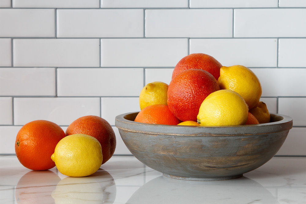Oranges and lemons in and out of bowl.