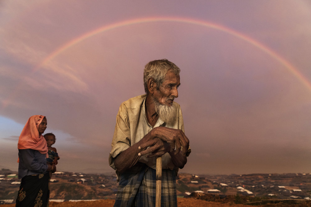 PAULA BRONSTEIN |  www.paulaphoto.com  |  @pbbphoto   Rohingya refugee Abu Siddique, 90, stands on a hill overlooking the Kutupalong refugee camp as a rainbow covers the sky. He had to pay people to carry him across the Myanmar border to Bangladesh, spending all of his savings. Over 630,00 Rohingya refugees have fled into Bangladesh since late August during the outbreak of violence in the Rakhine state, with a reported 1,000 dead.