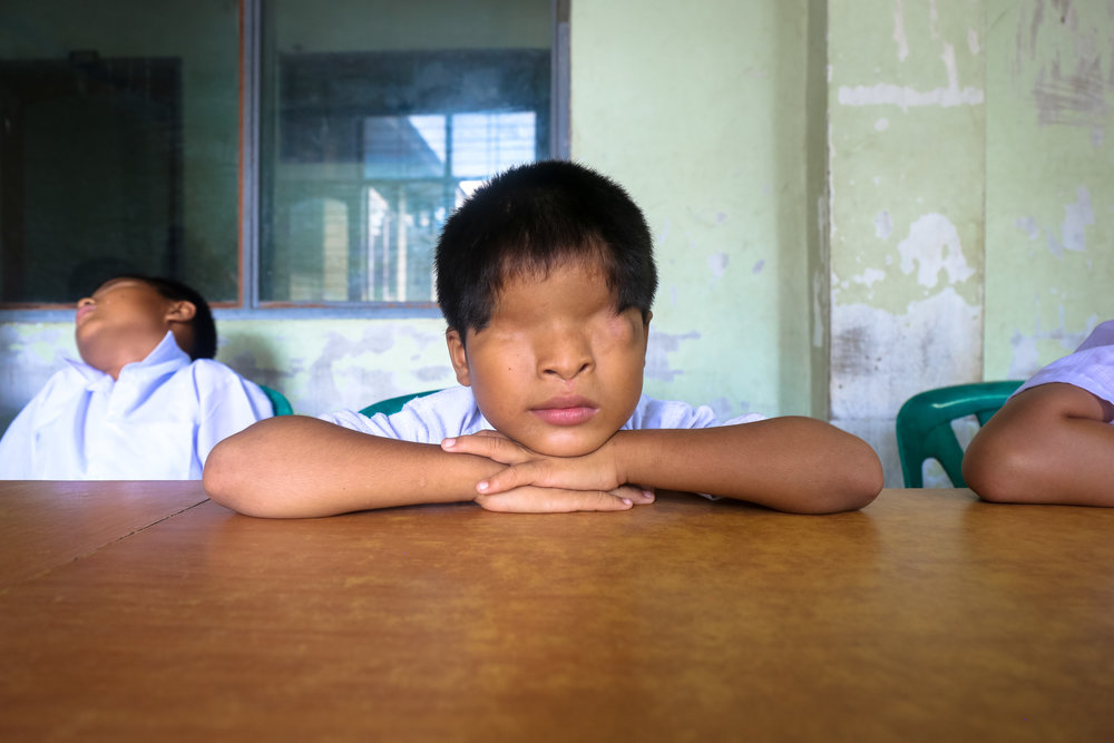 VICTORIA MILKO |  www.victoriamilkophoto.com  |  @thevmilko   A pupil at the Kyi Myin Dine School for the Blind in Yangon, Myanmar, listens to his teacher lecture about Burmese history. The school provides the opportunity for education, housing, and vocational training for visually impaired youth.