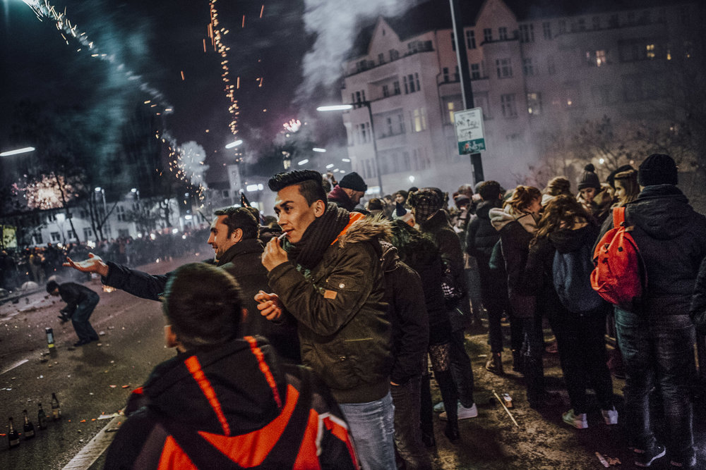 "KATJA HEINEMANN |  www.katjaheinemann.com  |  @hei_katja   Mohsen lights up while watching Berlin's fireworks for the New Year celebration. From ""Generation Exile"" -- a chronicle of young Afghan refugees coming of age in Germany."