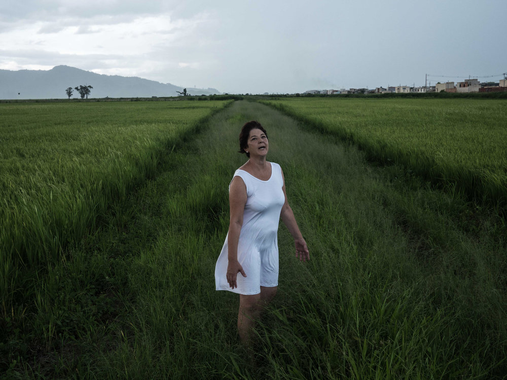 "ISABELLA LANAVE  www.isabellalanave.com  |  @isalanave   Sueli de Fátima, my mother, in a rice field on January 15, 2018. When I was ten, my mother was diagnosed with bipolar disorder and it was only in the past two years that we started talking about our feelings surrounding it. Fatima became the subject of a long-term project centered on our relationship. Getting closer to each other became less painful than moving away. Kay Jamison, a psychiatrist with bipolar disorder, wrote in her book ""Unquiet Mind"" that the feeling about this illness is like a poem from Dylan Thomas: ""The force that through the green fuse drives the flower/Drives my green age; that blasts the roots of trees/Is my destroyer."" These words inspired us to make this photo."