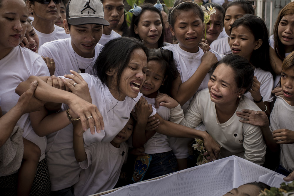 "ELOISA LOPEZ  www.eloisalopez.com  |  @eloisalopez   Relatives hold on to Michelle Pineda as she mourns over the casket of her 13-year-old son Aldrinne during his funeral on March 14, 2018 in Tondo, Manila, Philippines. Pineda was killed by a policeman after supposedly firing his gun ""accidentally."" Pineda is only one of the many children killed over the two-year course of the Philippine government's war on drugs.  From Rappler:    Tondo Teenager Killed by Manila Cop Buried; Family Seeks Justice"