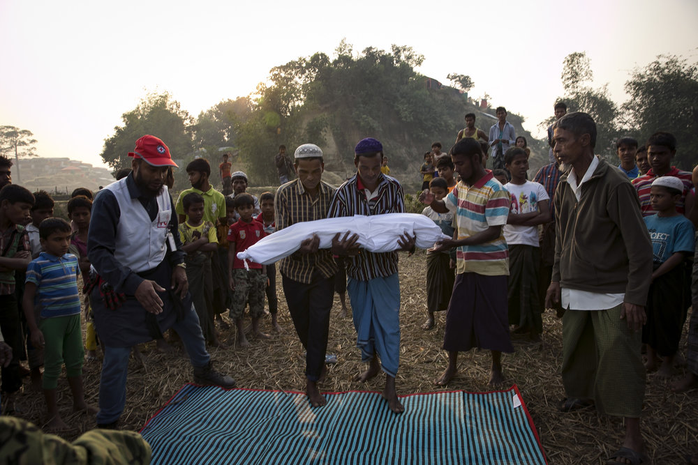 ALLISON JOYCE  www.allisonjoyce.com  |  @allisonsarahjoyce   The bodies of Rohingya refugees are carried for burial in Balukhali camp on January 12, 2018 in Cox's Bazar, Bangladesh. 30 year old Nurhaba, 8 year old Amin Sarif, 5 year old Dilsan Bibe and 1.5 year old Arjunan died in the late night of January 11th when their tent in a transit camp caught fire. Their family had arrived in Bangladesh 3 days earlier from Rasidong, Myanmar. They left their village 18 days ago after the Myanmar military and local Buddhist beat Nurhaba's husband, Adbul Rahim, and refused to let him harvest his fields. For 15 days they walked to the border and took shelter in other villages, with hardly enough food or water to sustain them along the way. When they were finally able to cross over into Bangladesh by boat, Abdul Rahman said they felt happy and confident about their future. Over 650,000 Rohingya have crossed the border to Bangladesh since August last year, fleeing the violence at Rakhine State when their villages were attacked and many worry that they will face further reprisals if they return to Myanmar.