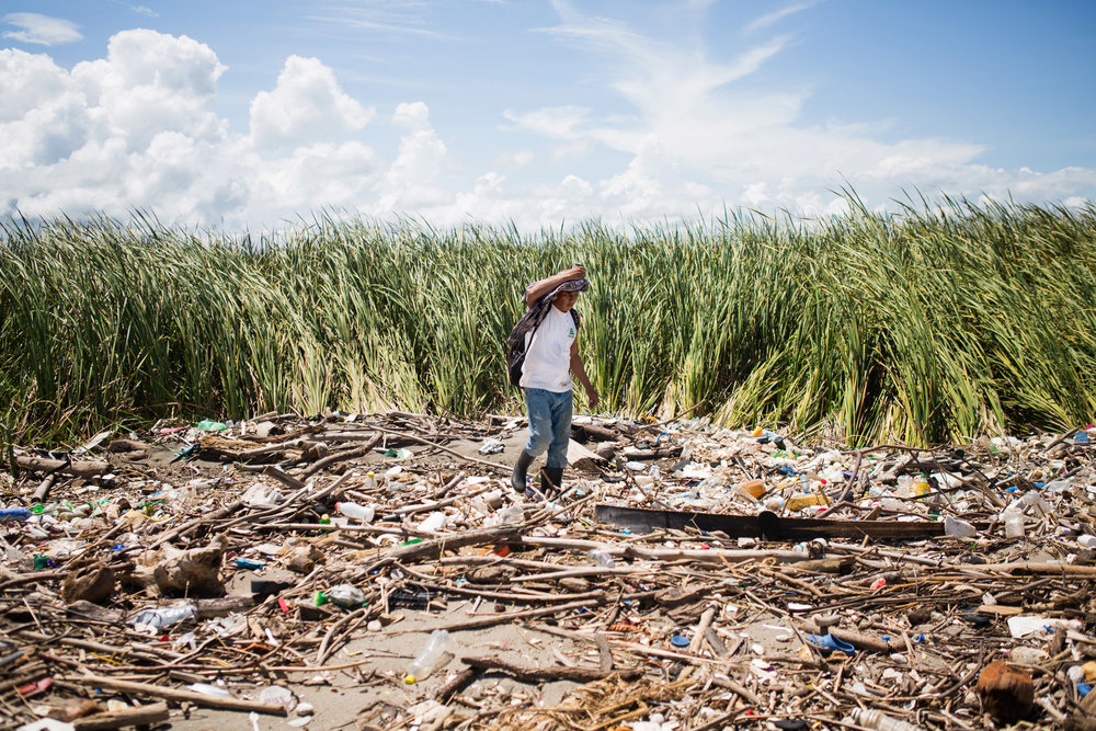 CELIA TALBOT TOBIN  www.cttobin.com  |  @cttobin   Josua Dubón García, an employee of Guatemala's National Council for Protected Areas, walks along a beach at the mouth of the Motagua River on the Caribbean coast. In 2018, Honduras threatened to bring a lawsuit against Guatemala for the mountains of trash that wash up on its beaches every rainy season. The Motagua runs more than 400 kilometers, from the remote mountains of Chichicastenango, through the capital city with its three million residents, and into the Caribbean, where its waters meet the second-longest barrier reef in the world.