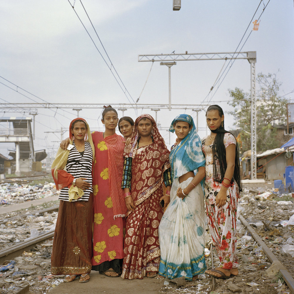 "SARA HYLTON  www.sarahylton.com  |  @sarahyltonphoto   Radhika's ""daughters"" as she affectionately calls them pose for a portrait near their shared settlement outside of Mahim train station in Mumbai, India. The hijra community in Mumbai is predominantly hierarchical, where more experienced and mature hijras, like Radhika, act as guardians and superiors to younger hijras. India's hijra community includes transgender and intersex people. It is believed by many Indians that hijras have the capacity to bless or curse, and hijras exist in this grey zone -- making a living by crashing weddings and birth ceremonies, begging, and sometimes through prostitution. Indian culture has long recognized the fluidity of gender, with a number of demigods in Hindu scripture described as being a third gender. Yet, homesexuality remains taboo and hijras are often forced to live underground, being ostracized by their family and friends. Because of this, India's hijra community maintains a hierarchical, somewhat secretive subculture.  From The New York Times:    The Peculiar Position of India's Third Gender"