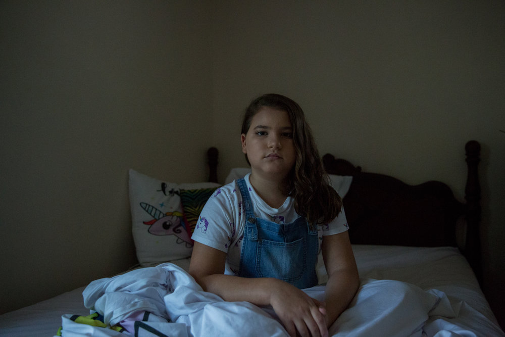 ANNA CLARE SPELMAN  www.annaclarespelman.com  |  @annaclarespelman   Maddie, 11, sits for a portrait in her bedroom in North Carolina on July 26, 2018. Maddie is transgender, and publicly transitioned at the age of six. She loves unicorns and collects clothes, toys, and accessories that have anything to do with unicorns.