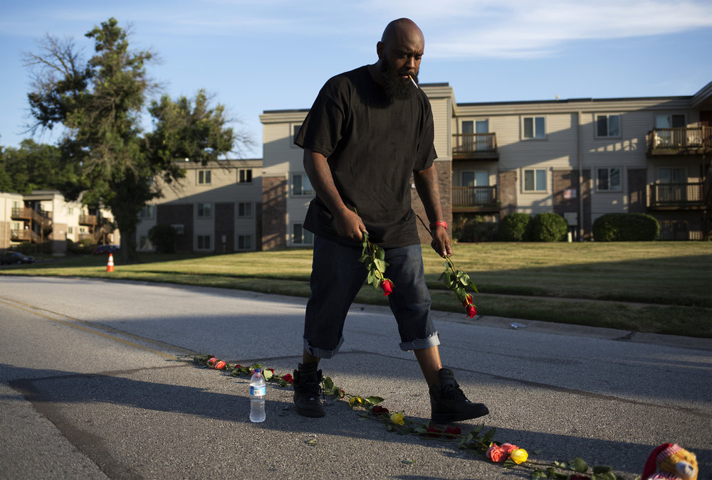 CAROLINA HIDALGO  www.carolina-hidalgo.com  |  @carolinahidalgo   Michael Brown Sr. sets down roses as he rebuilds a memorial to honor his son, Michael Brown Jr., on Canfield Drive in Ferguson on Aug. 8, 2018. With help from family and friends and community members, Brown rebuilds the memorial every year before the anniversary of the day a Ferguson police officer killed his son.