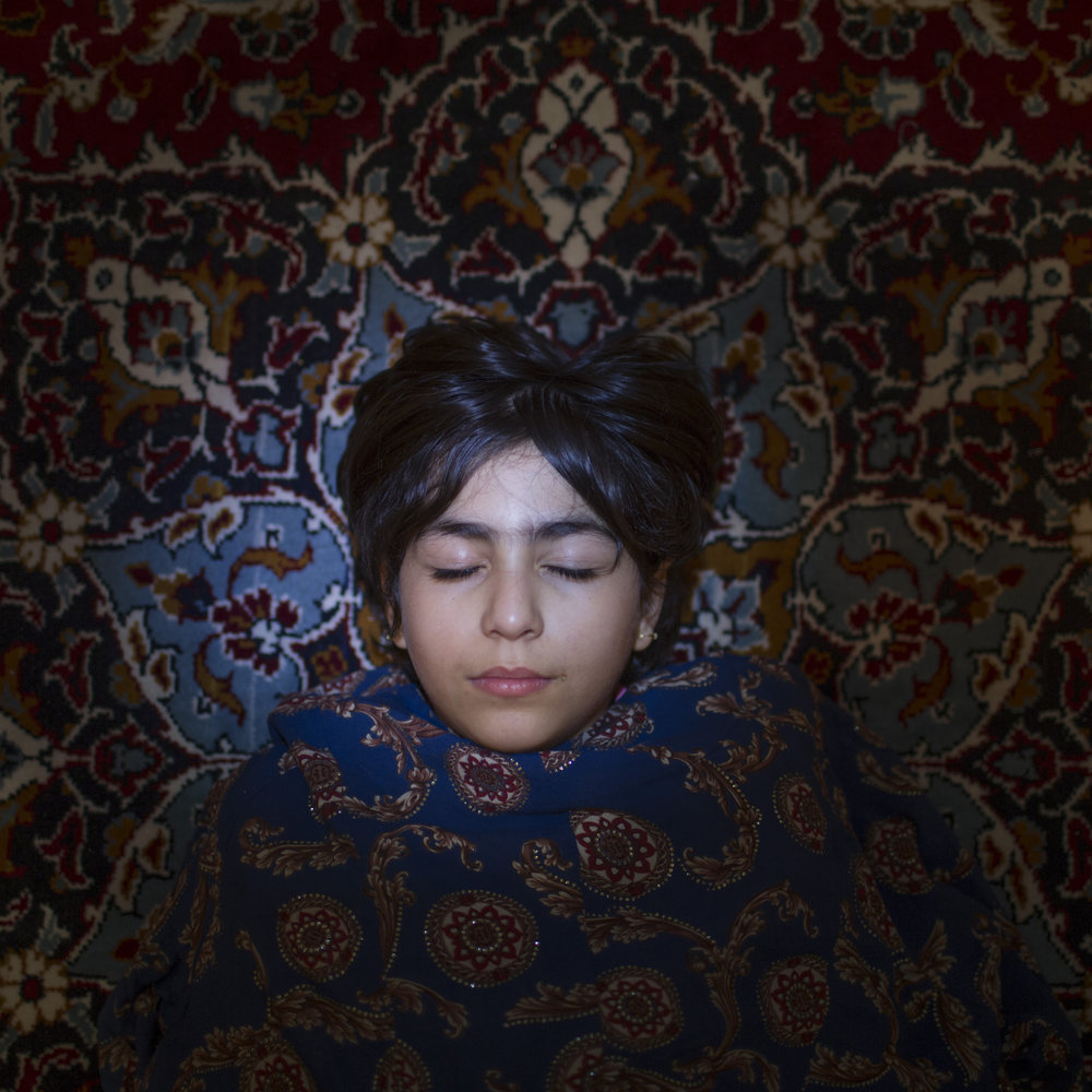 "MOJGAN GHANBARI  www.mojganghanbari.com  |  @mojganghanbari_   Setayesh lays on the carpet in her grand mother's home. inTehran, Iran. Setayesh says: ""I want to be a dentist when I get older and make money.""   From ""The Wall,"" an ongoing project which seeks to start a dialogue between Iranian mothers and daughters.   From The New York Times:    Bridging the Gap Between Mothers and Daughters in Iran"