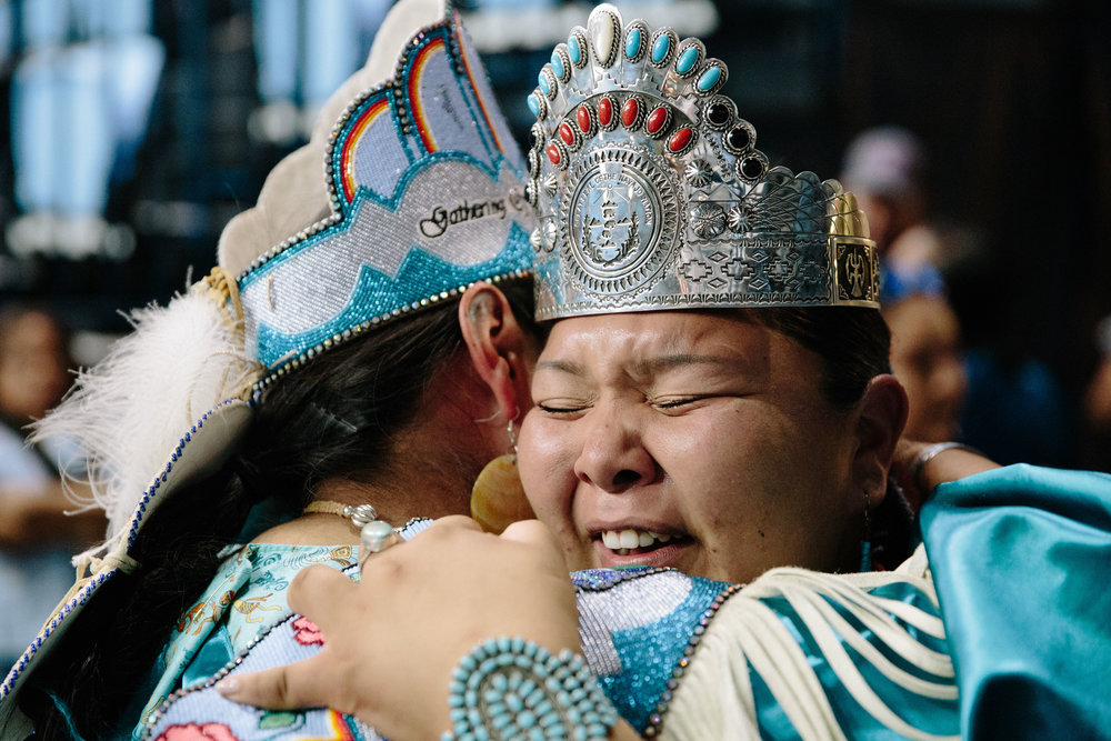 CAITLIN O'HARA  www.caitlinohara.com  |  @caitlin_oh   Newly-crowned Miss Navajo Nation 2018-2019 Autumn Montoya, right, hugs 2018-2019 Miss Indian World Taylor Susan, left, after the coronation ceremony at Bee Hóltzl Fighting Scouts Event Arena in Ft. Defiance, Arizona in Navajo Nation on Saturday Sept. 8, 2018. Montoya and Susan competed together at the Miss Indian World pageant at the 2018 Gathering of Nations.  From NPR:    Becoming Miss Navajo Nation