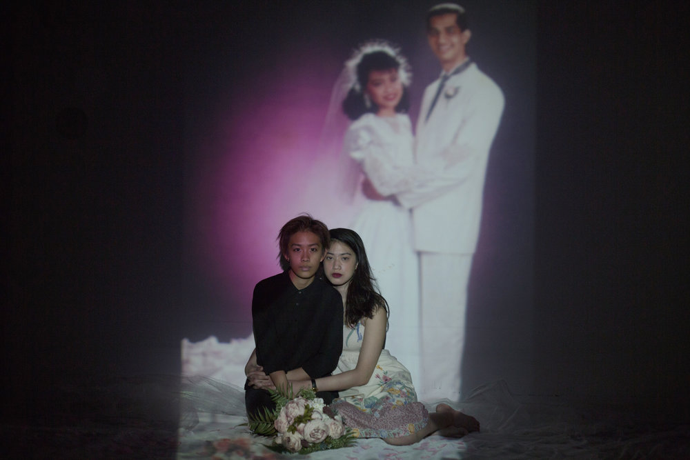 CHARMAINE POH  www.charmainepoh.com  |  @psxcharmaine   Jean Goh and Xener Gill pose for a portrait, with Xener's parents' wedding portrait projected onto the backdrop. Jean met her first few partners through church. While she still believes in God, she decided to step back from serving in the church she attended, partially because the institution disapproved of homosexuality. Jean identifies as gender queer. It is Xener's first relationship with a woman.