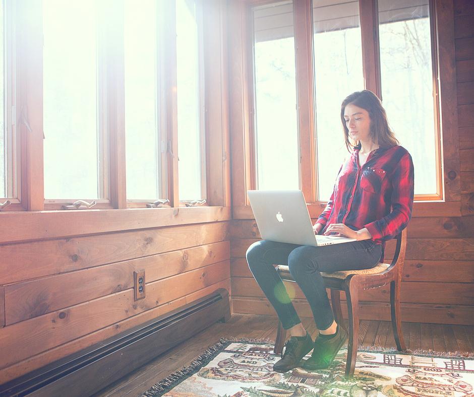Femme assiste avec un Mac book sur les jambes
