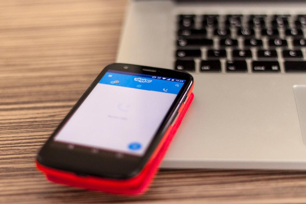 Smartphone posée sur un Macbook avec application Skype lancée.