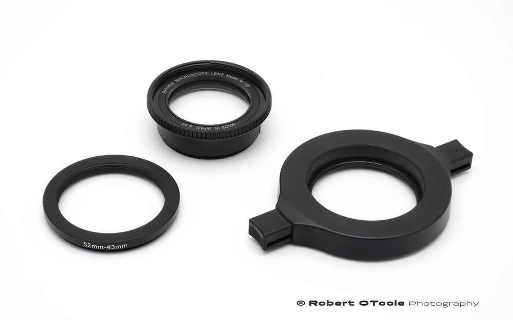 Aluminum 52mm - 43mm step down ring, Raynox DCR-150 and Raynox adjustable adapter on the right.