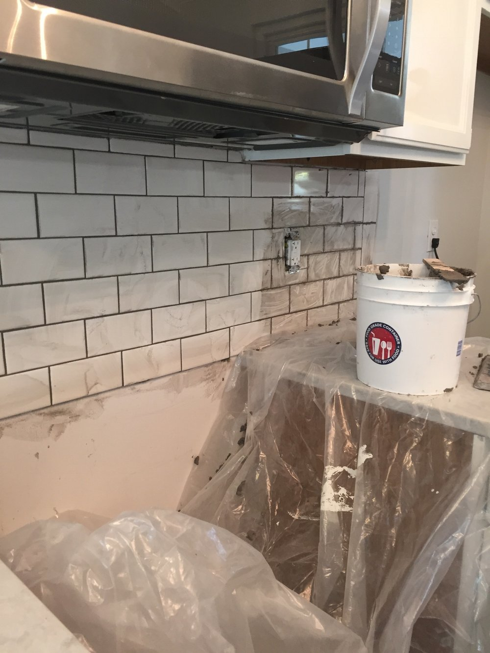 added subway tile backsplash with gray grout