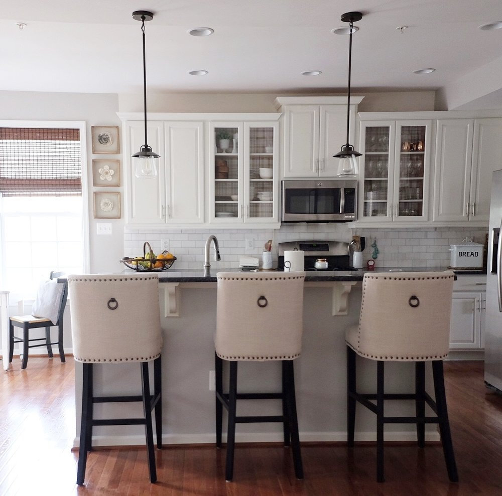 paint: Shell White SW 917 (satin finish) ; stools: pier 1 imports, backsplash: Carrara marble; pendants: Lowe's