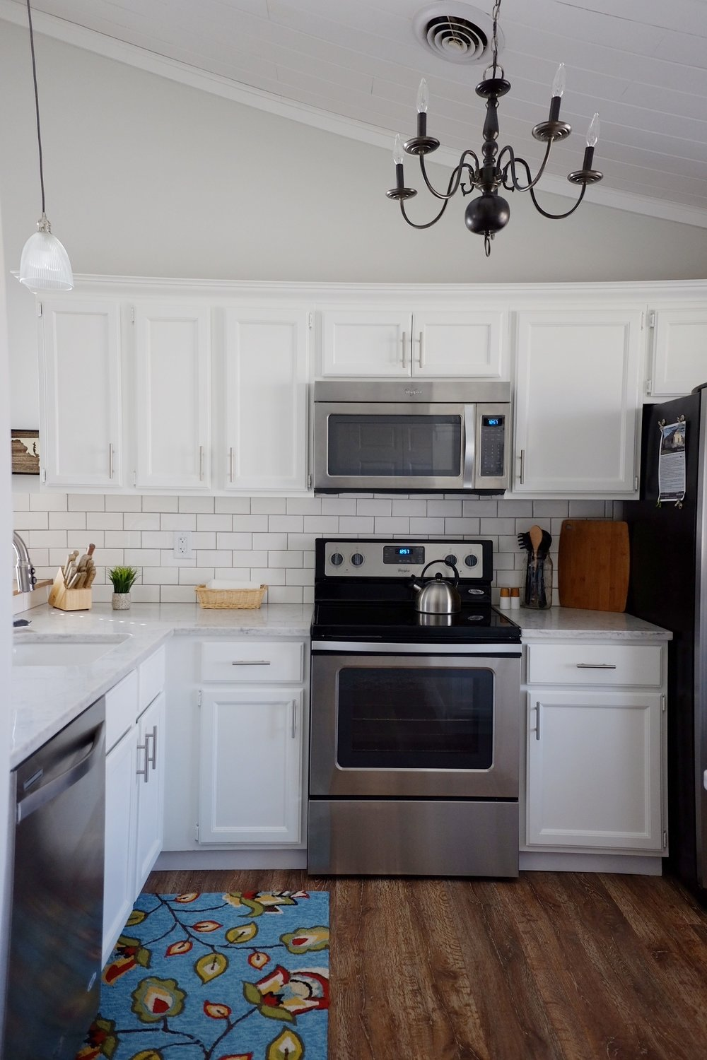 Paint: Valspar cabinet paint -pure white (semi-gloss), rug: TJ MAXX, Chandalier: Home Depot (spray-painted black); pendant lights: lowe's; backsplash: white subway tile w/DeLorean Gray grout)