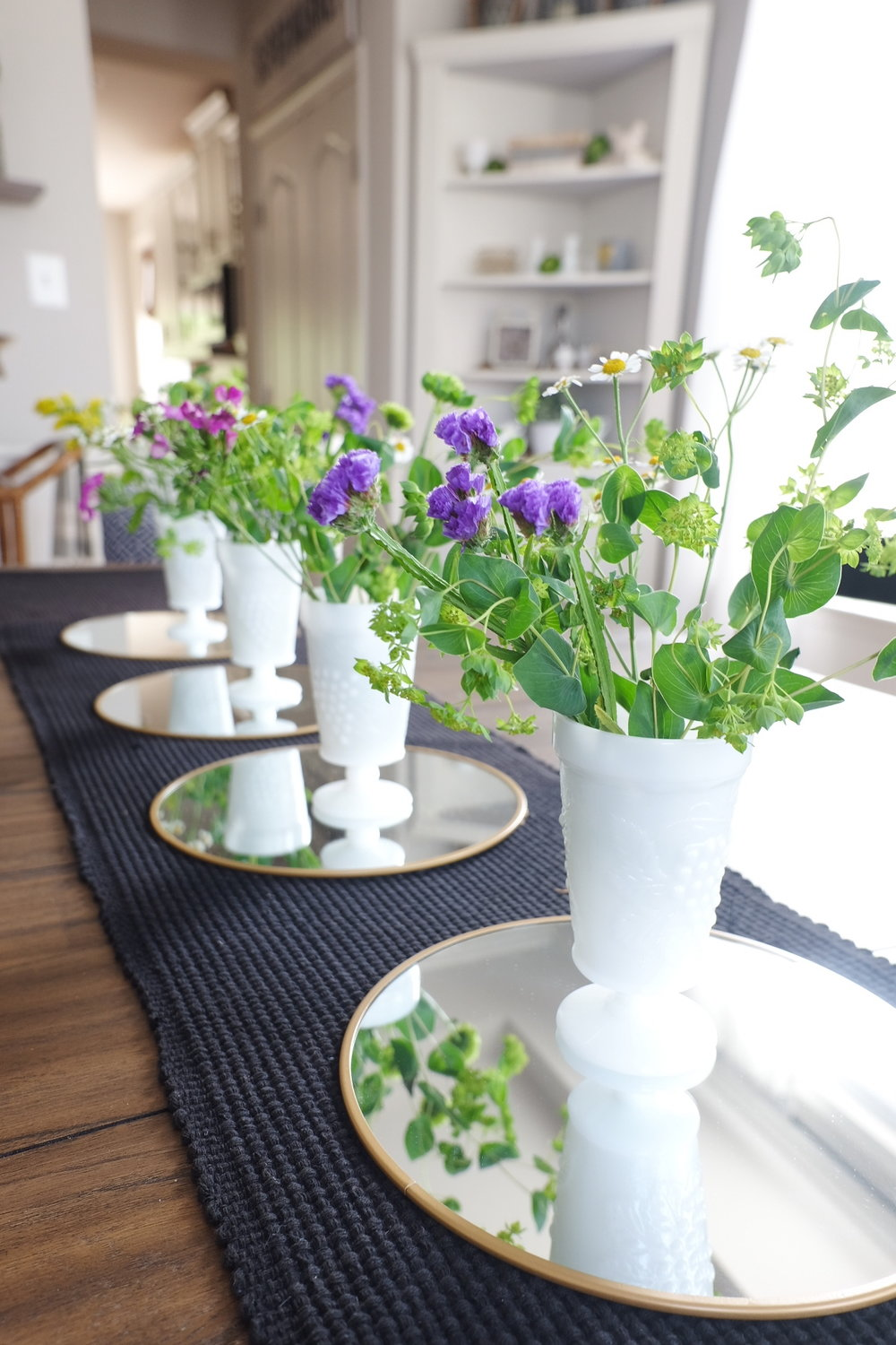 Placing mirrors underneath your jars of Spring flowers make a great centerpiece!