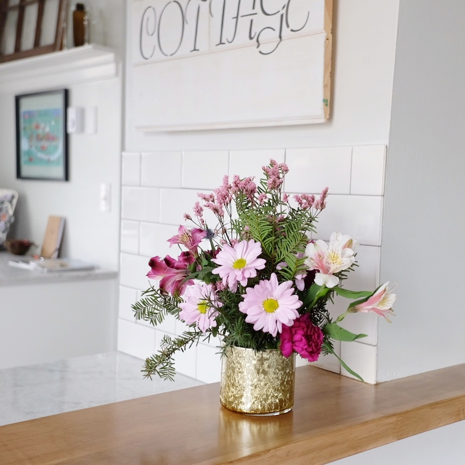 Use a candle jar as a vase for Spring flowers.
