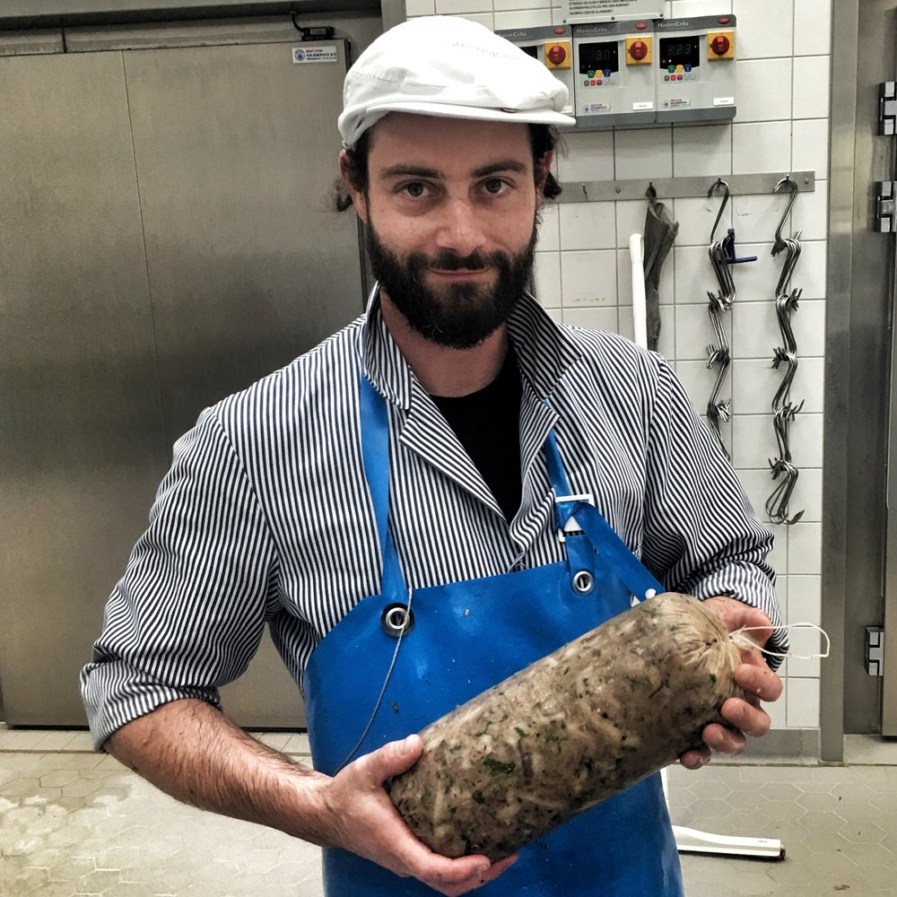 Ollie, the German butcher holding a Coppa di Testa, an Italian version of headcheese.