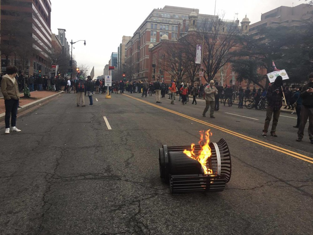 Trash can lit on fire by protesters, K Street.