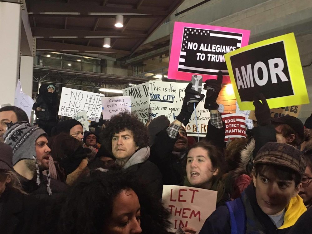 Crowd of protesters chant and wave their signs, John F. Kennedy International Airport Terminal 4.