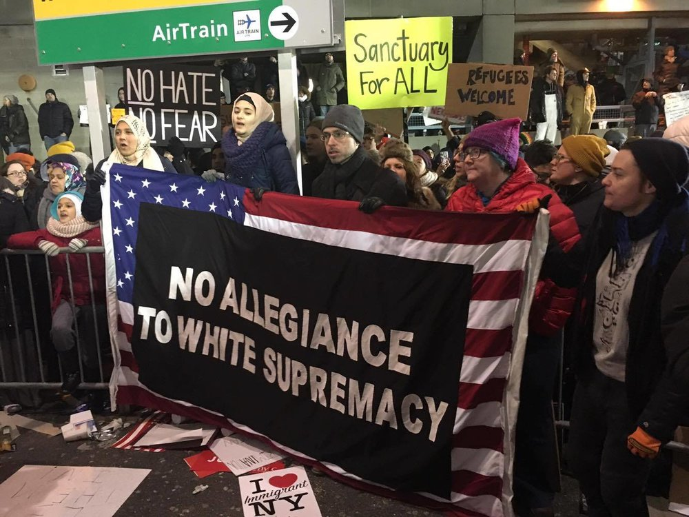 Protesters chant and display altered US flag, John F. Kennedy International Airport Terminal 4.