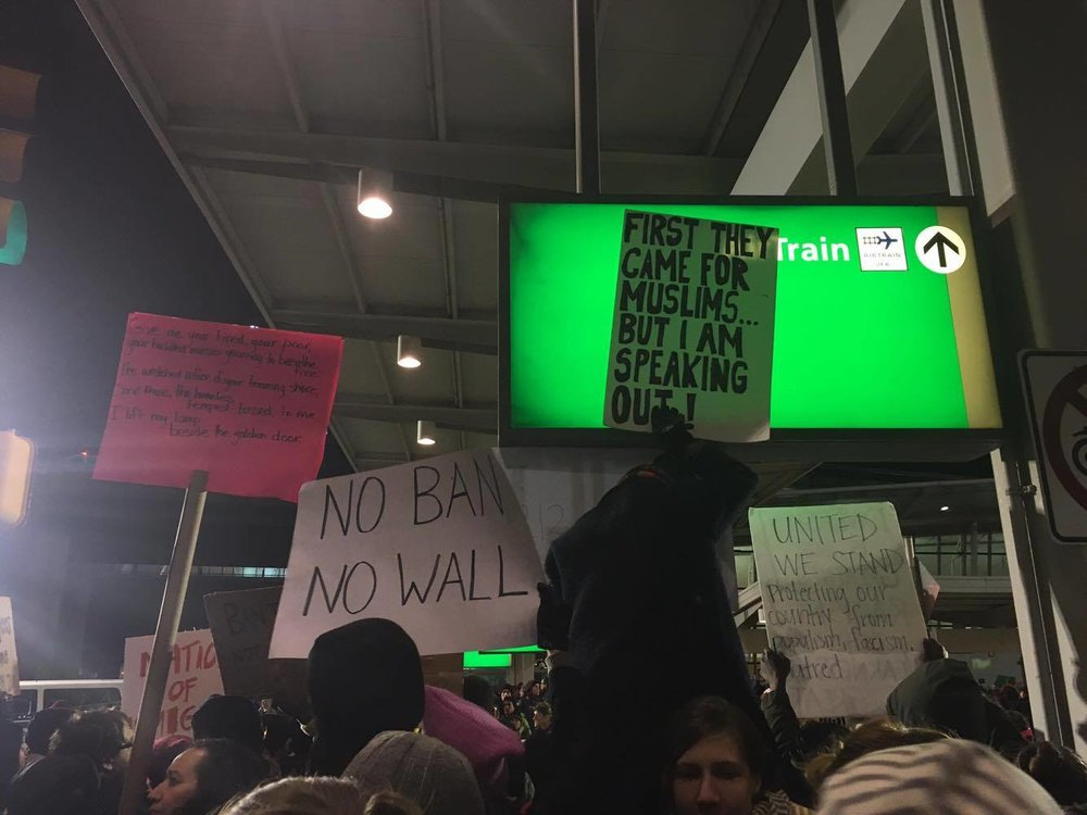 Protester placing placard on illuminated airport sign, John F. Kennedy International Airport Terminal 4.